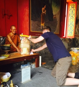 My first-cousin-once-removed offers gift to monk in nearby Surin temple.